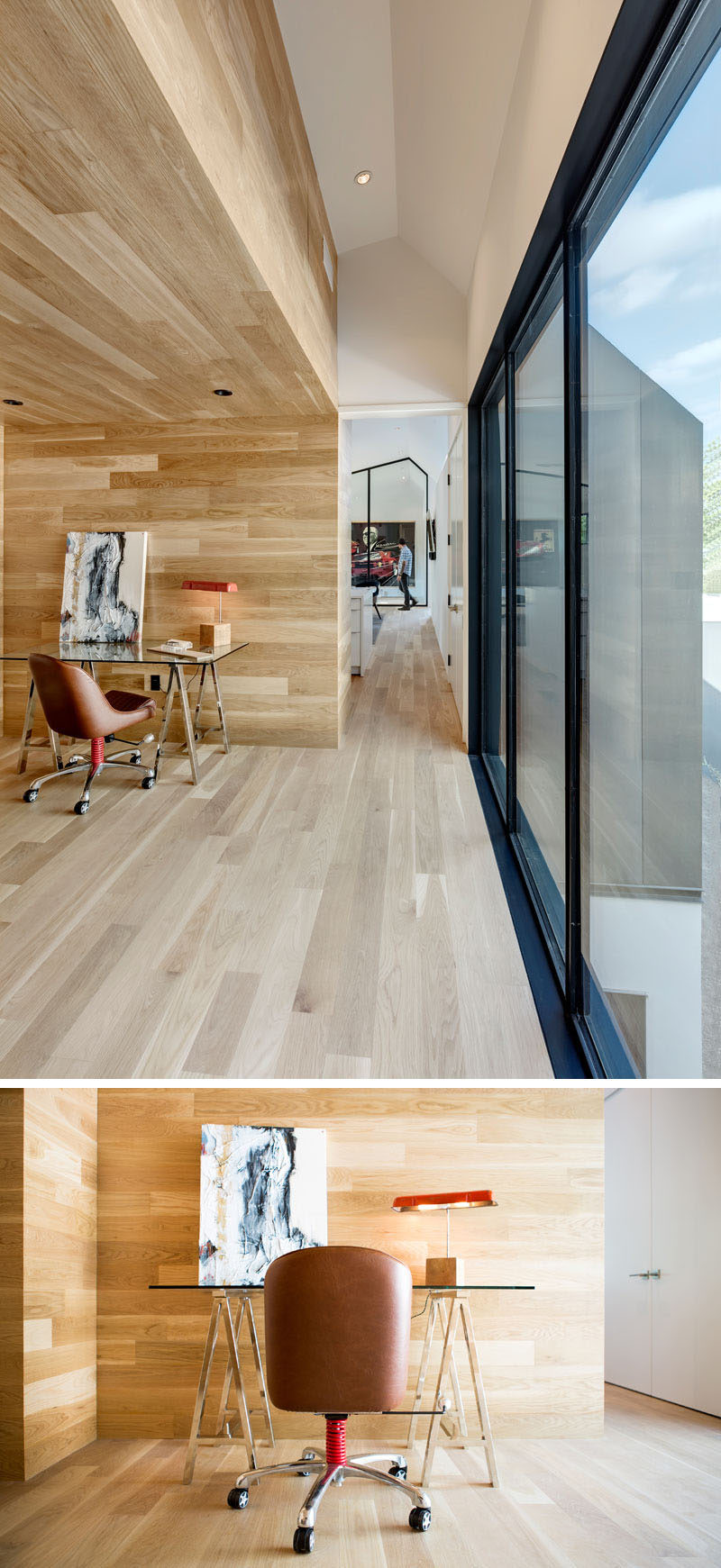 This modern house has a small hallway that leads to a home office nook surrounded by wood. #HomeOffice #OfficeNook #InteriorDesign