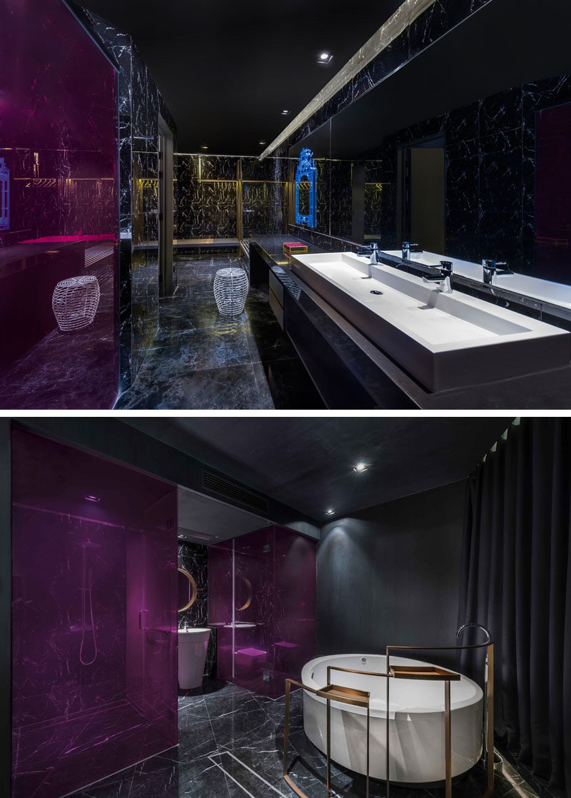 This modern hotel athroom features bright pink panels, while the bath can be closed off the hotel room with the use of curtains. #ModernBathroom #HotelBathroom #BlackBathroom