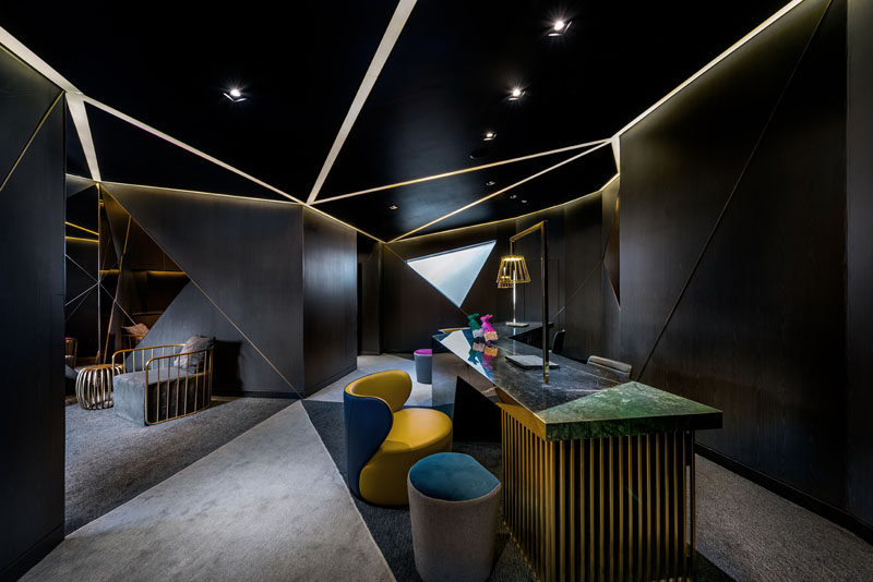 This dark hotel reception area is full of angles and lines of light that create a bold first impression. #HotelReception #Lighting