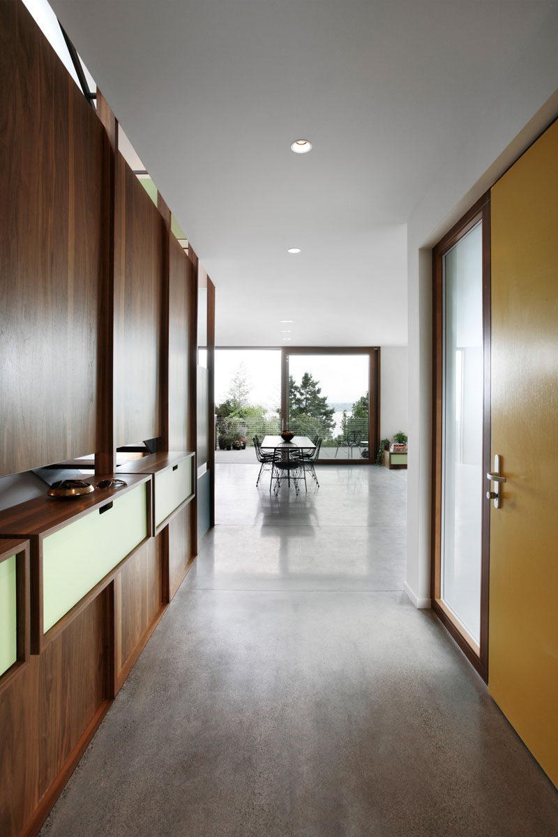 Stepping inside this modern house, there's a walnut accent wall with built-in shelving and a hallway leads to the main floor of the home. #YellowFrontDoor #Entryway