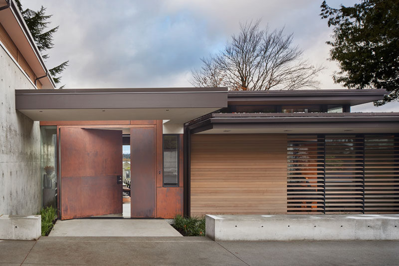 This modern house has a large, pivoting steel front door. #PivotingDoor #ModernHouse #FrontDoor