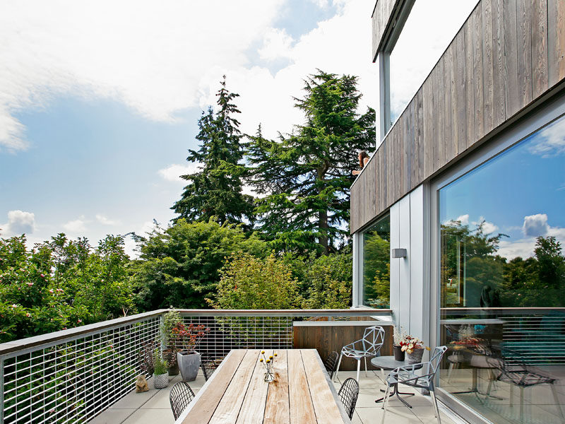 This modern house has a deck off the main living area, that provides views of the surrounding neighborhood. #Deck #ModernHouse