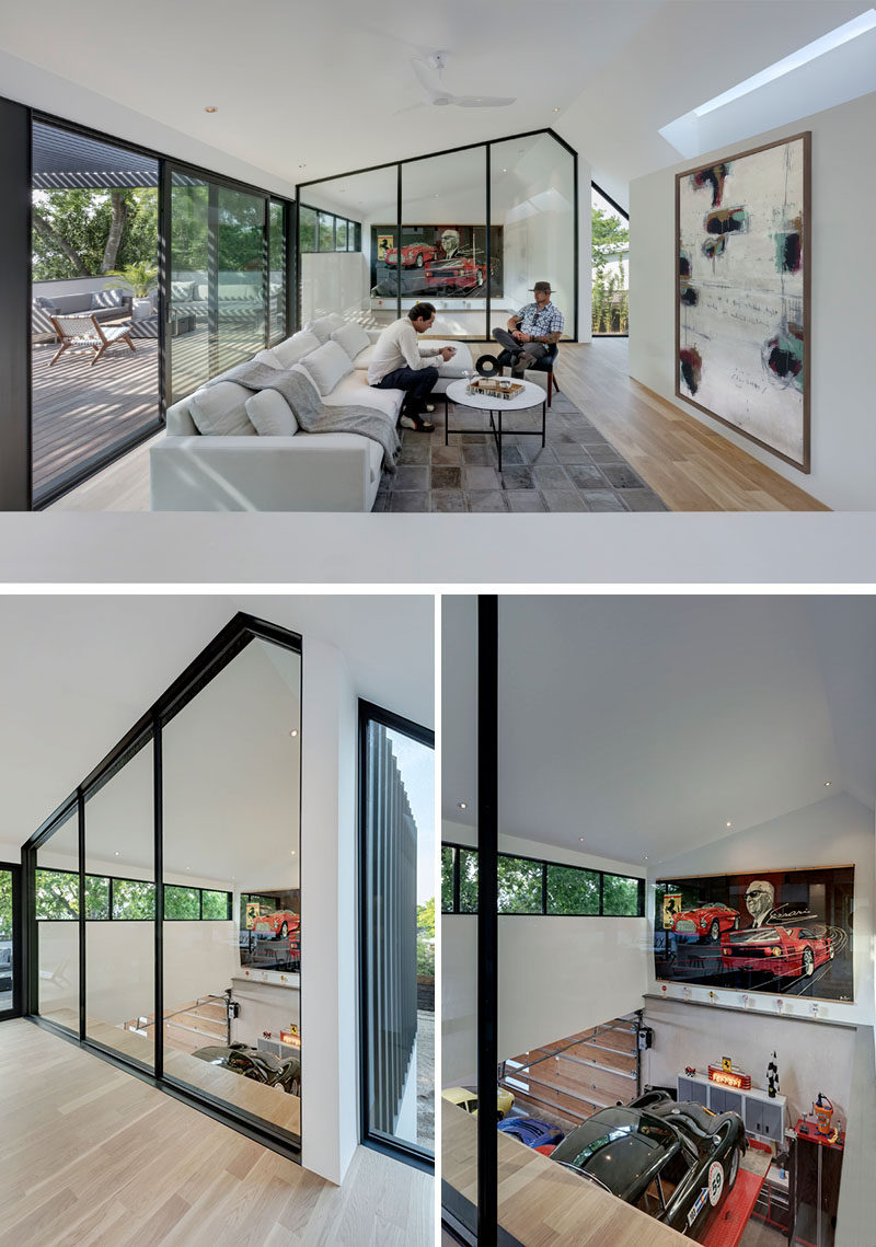 At the top of the stairs in this modern house, there's a large black-framed glass wall that provides a view of the collector cars in the garage below. #InteriorGlassWalls #GlassWalls #Windows