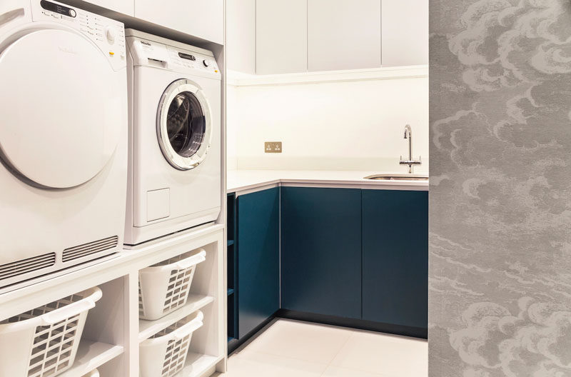 This modern utility room features white and dark blue matte cabinetry, a washer and dryer that have been raised so there's no need to bend down when moving the washing to the dryer. #ModernLaundry #LaundryRoom