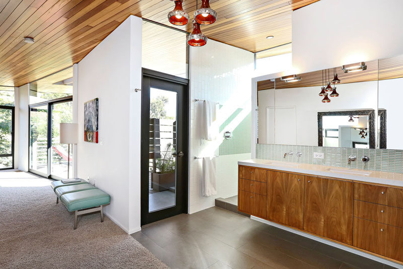 This modern master bedroom also has its own bathroom that's somewhat open to the rest of the room. A large double vanity sits next to the indoor shower, while through the black-framed glass door is an outdoor shower. #BathroomDesign #ModernBathroom