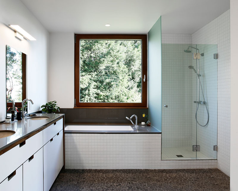 In this modern master bathroom, there's a walk-in shower with a glass surround, and a built-in bathtub that's positioned underneath the window. #MasterBathroom #WalkInShower #BuiltInBathtub
