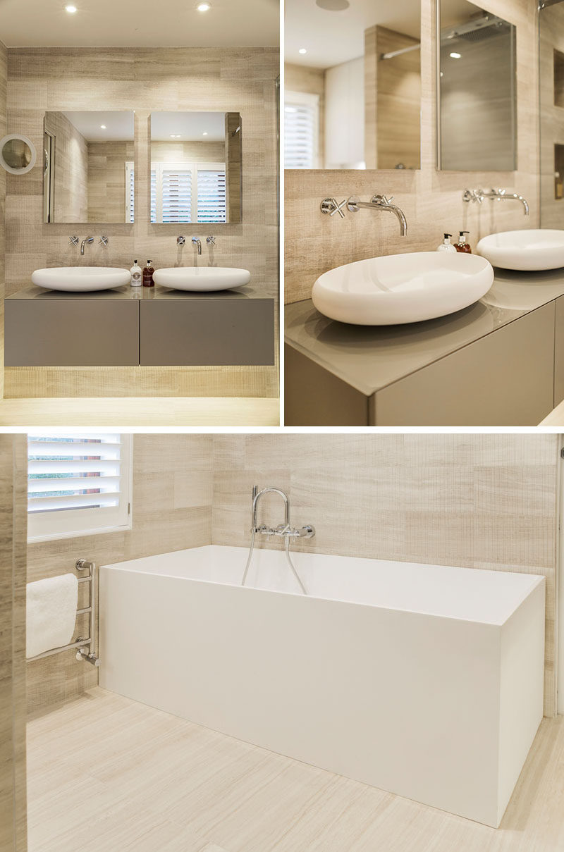 This modern master ensuite bathroom features a natural and luxurious appearance, with light and natural colors, while touches of white draw attention to the curved sinks and the rectangular bathtub. #MasterBathroom #BathroomDesign