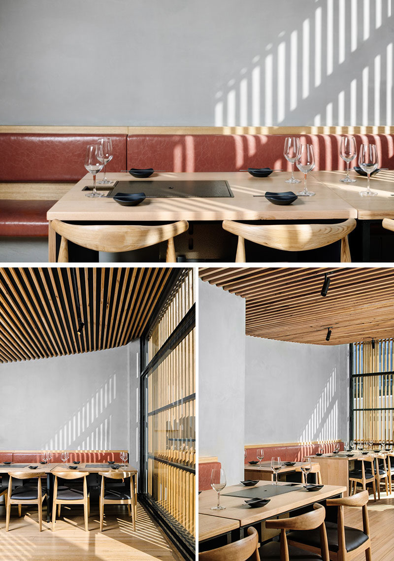 The interior of this modern Korean BBQ restaurant has soft grey walls and banquette seating with two banks of timber tables with integrated charcoal barbecues. Instead of having pendant lights hanging above the tables, the designers installed LED backlighting behind the banquettes. #RestaurantDesign #InteriorDesign