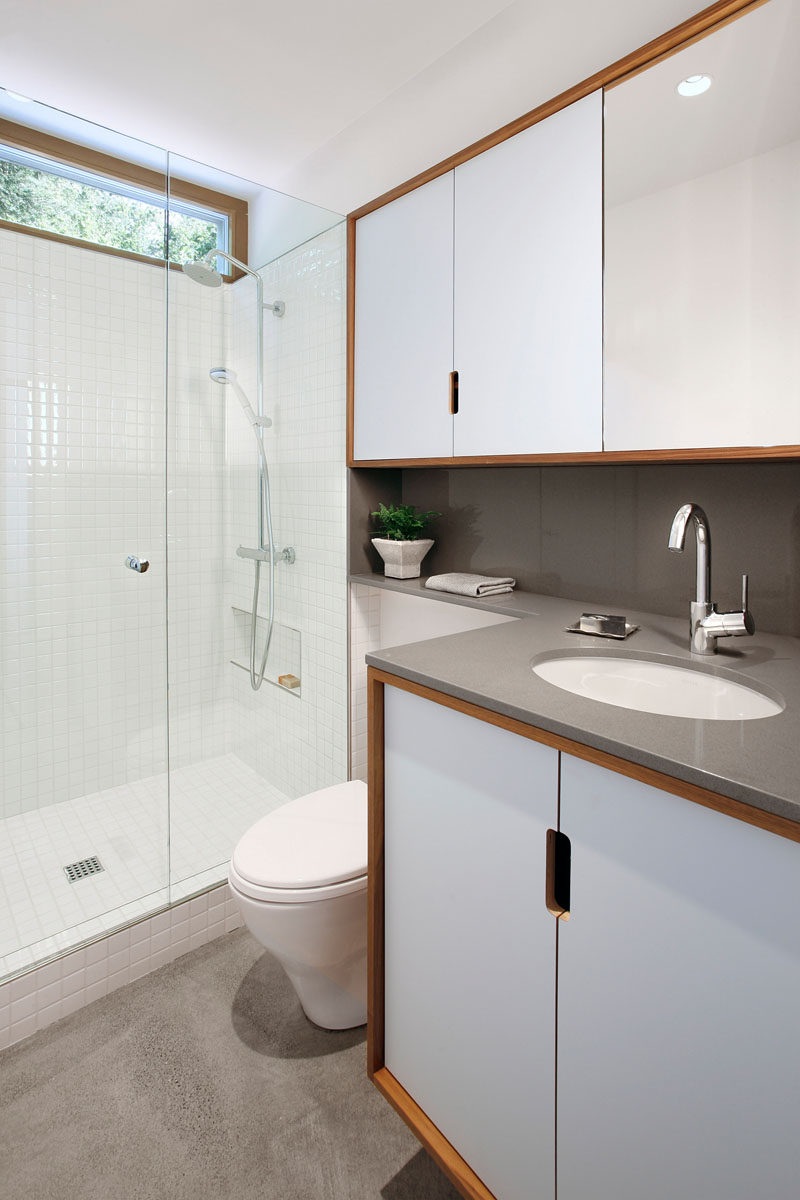 In this modern bathroom, a grey counter has been paired with white tiles, glass and wood frames to create a contemporary look. #ModernBathroom #BathroomDesign