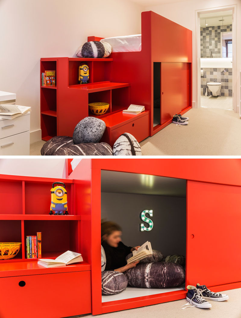 In this modern kids bedroom, a custom-designed, bright red bed unit was created with storage shelves, that double as stairs to the bed. Underneath the bed, there's a small den with sliding doors, creating a quiet reading nook. #KidsBedroom #BedroomDesign #TweenBedroom