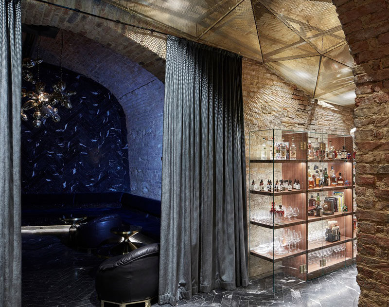 In this underground bar, there are numerous alcoves have a variety of seating options for guests. In this alcove, there's a darkened room with dark leather couches hidden by curtains. #UndergroundBar #BarDesign #InteriorDesign