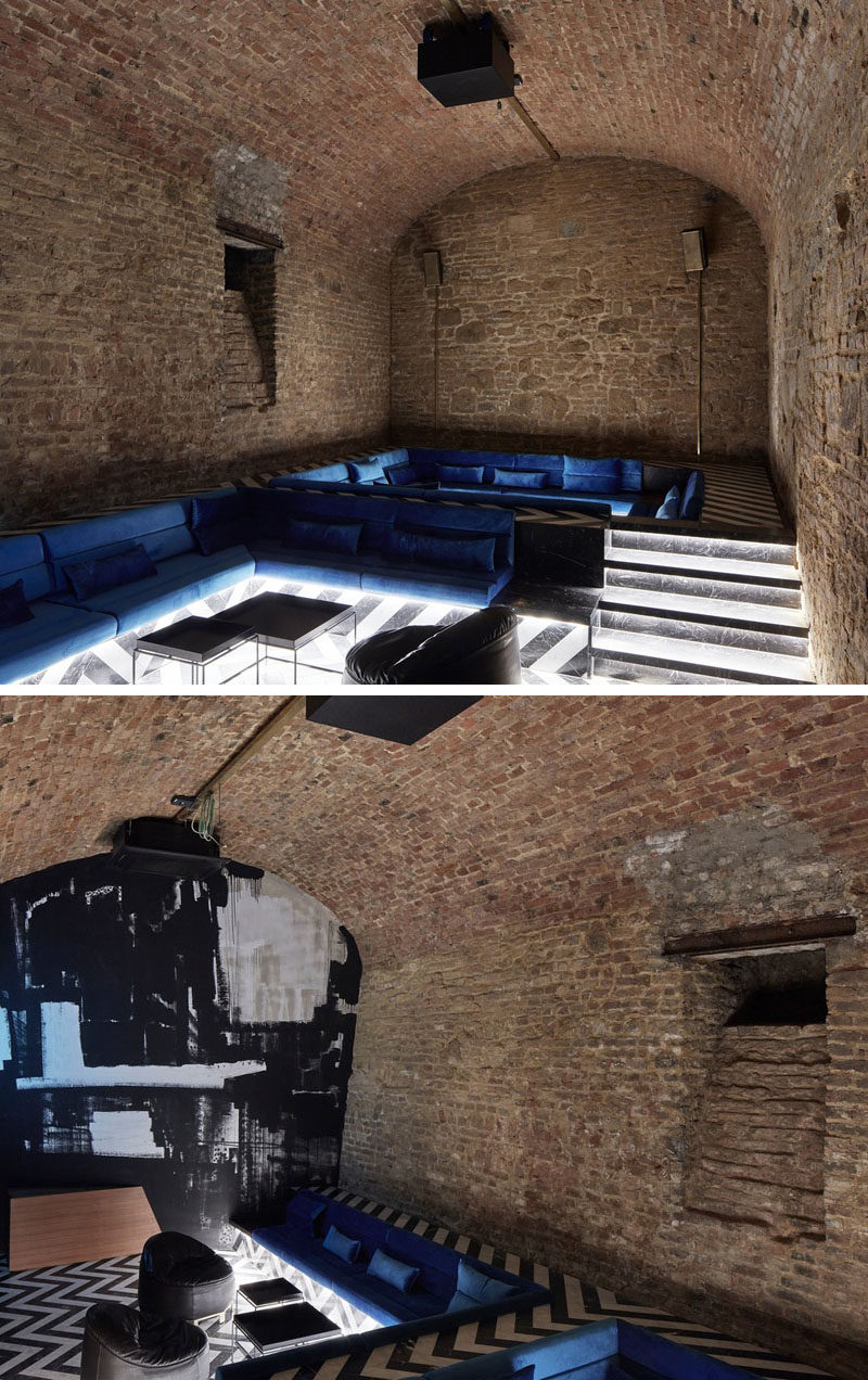 In this underground bar with stone alcoves, there's a raised floor that allows for a sunken lounge with blue couches and hidden lighting. #SunkenLounge #StoneAlcove #UndergroundBar