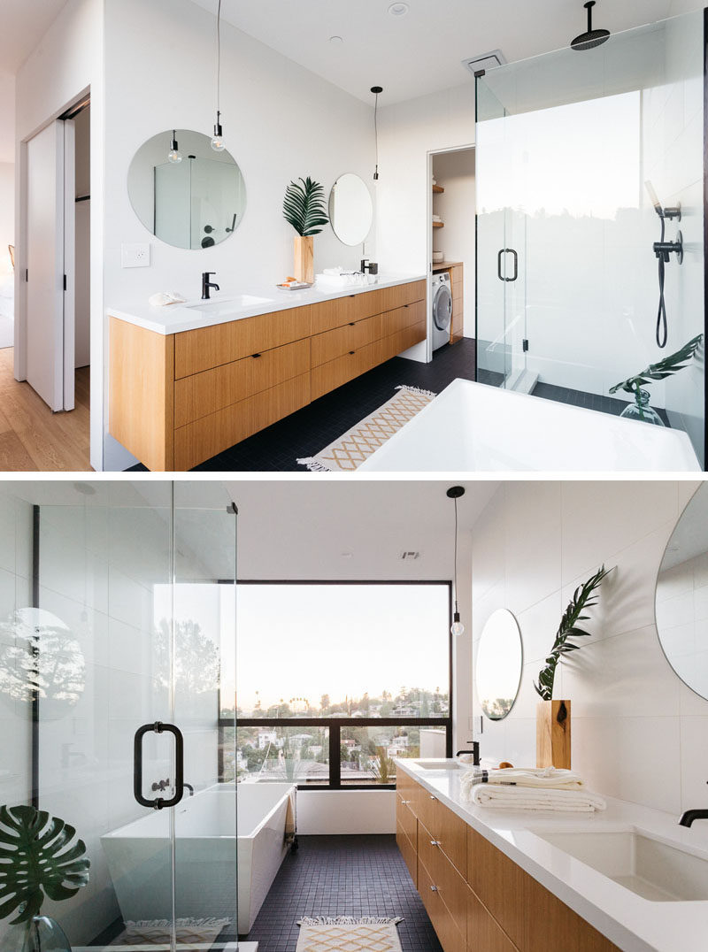 In this modern master bathroom, there's a large wood vanity with a white counter and round mirrors. Beside the vanity is a small nook with a laundry room, and opposite the vanity is the shower with a glass surround and a bathtub positioned to take advantage of the views. #MasterBathroom #BathroomDesign #ModernBathroom