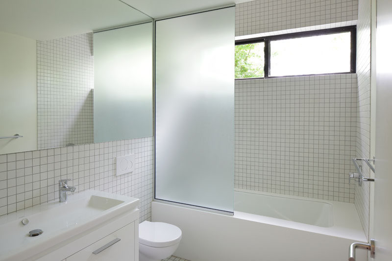 In this modern master bathroom, small square tiles cover the walls, while a frosted glass screen separates the bath/shower from the toilet and vanity. #MasterBathroom #BathroomDesign #ModernBathroom