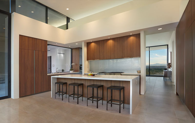 In this modern kitchen, wood cabinetry adds warmth to the space and a large island provides space for people to sit and relax. #ModernKitchen #KitchenDesign