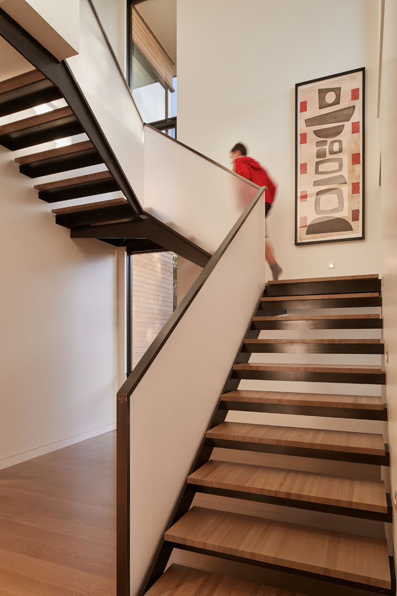 These modern stairs with wood treads features a frosted handrail. #Stairs #StairDesign