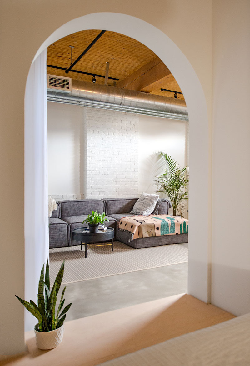 This modern loft has a living room that's been set up with a low couch, rug and a couple of plants.