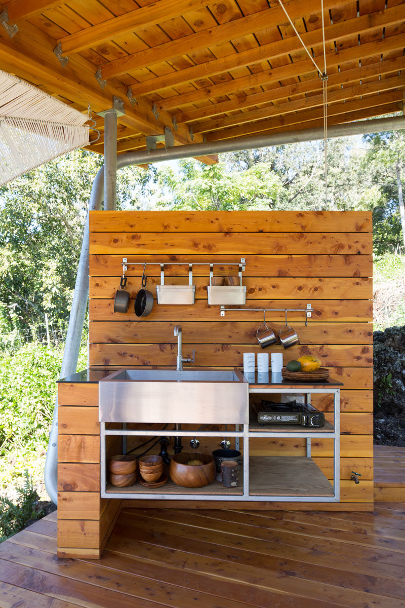 The outdoor pavilion also has a kitchen with a stainless steel shelving unit and sink. #OutdoorKitchen