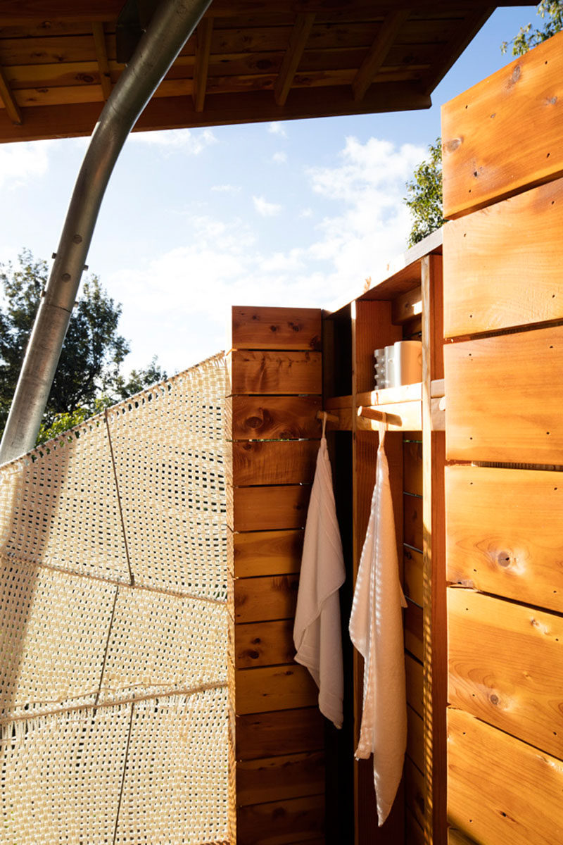 This modern outdoor pavilion has an open shower, with some privacy provided by a woven marine rope shaded panel that was created by the designer of the project. #WovenScreen #OutdoorShower