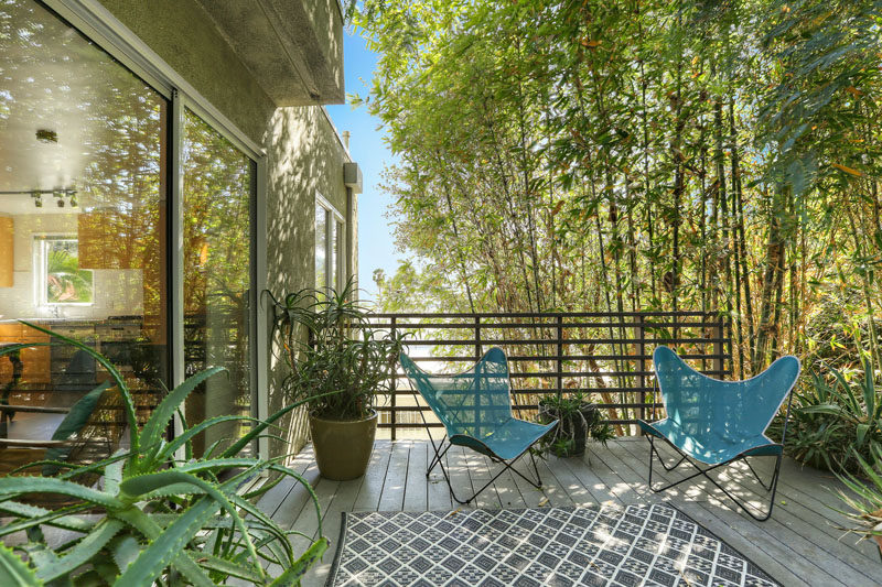 This private deck that's set up with planters and chairs, has views of the surrounding tall trees. #PrivateDeck #OutdoorSpace