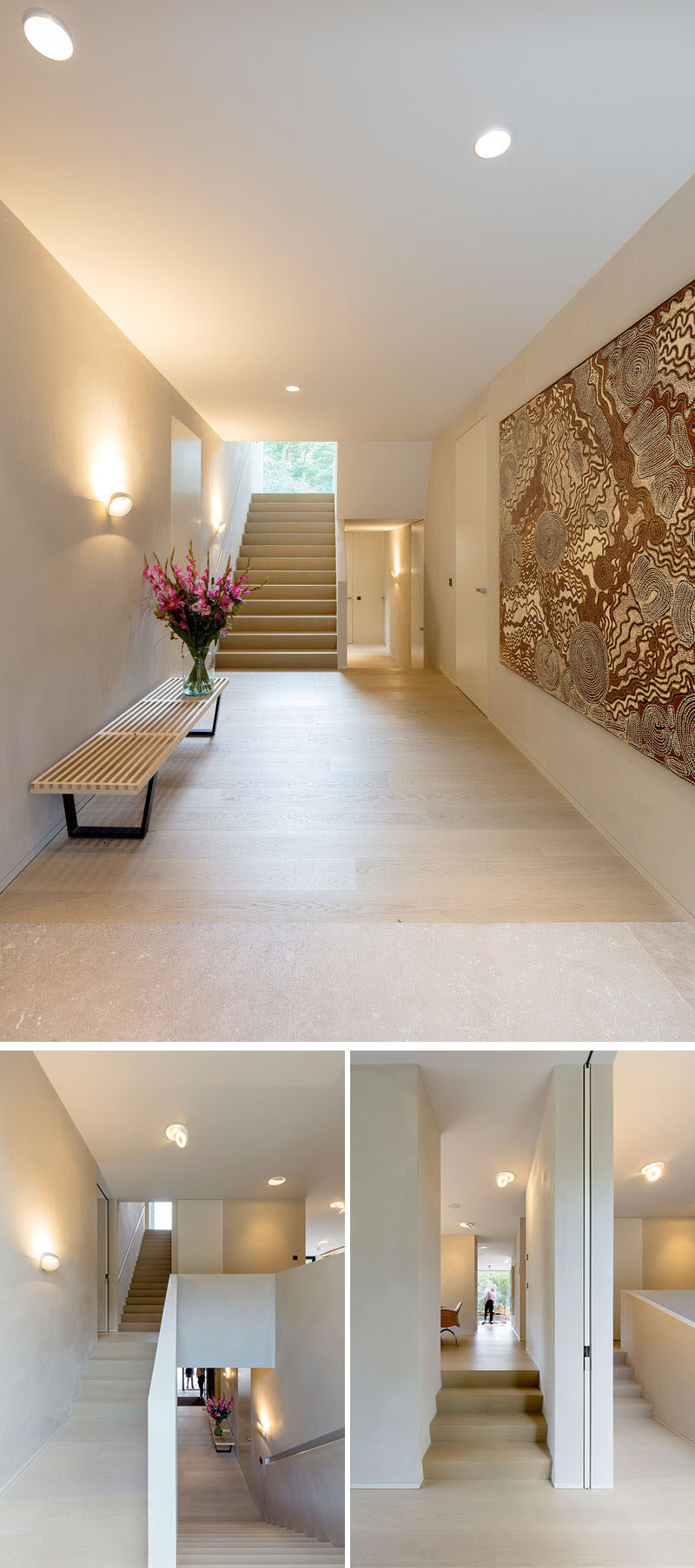 Stepping inside, the interior of this modern house is bright with light colored flooring, minimal furniture and wall art. Stairs lead to the different levels and areas of the house. #ModernHallway #Stairs