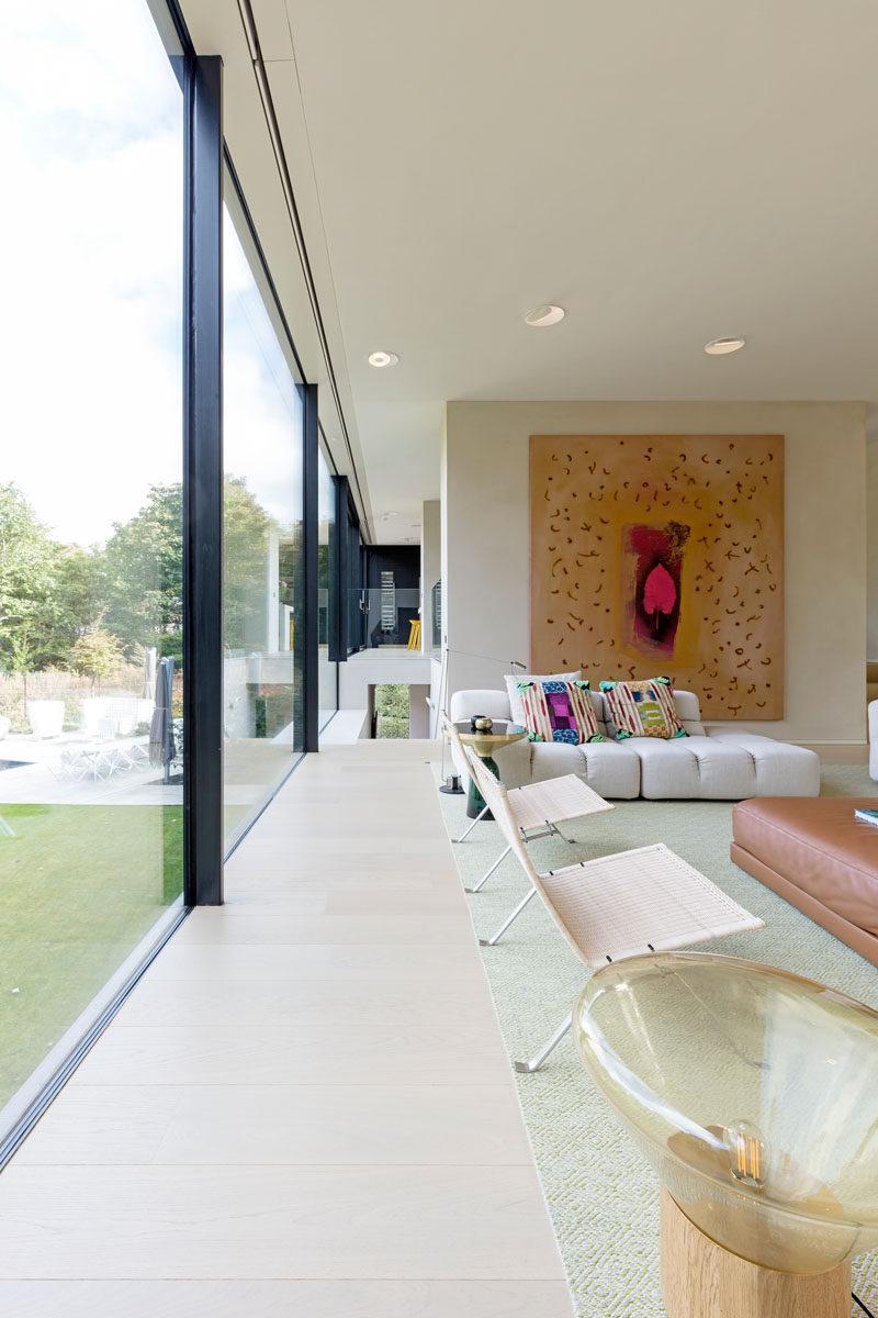 Floor-to-ceiling windows allow an abundance of natural light to flood this modern house. #FloorToCeilingWindows #InteriorDesign