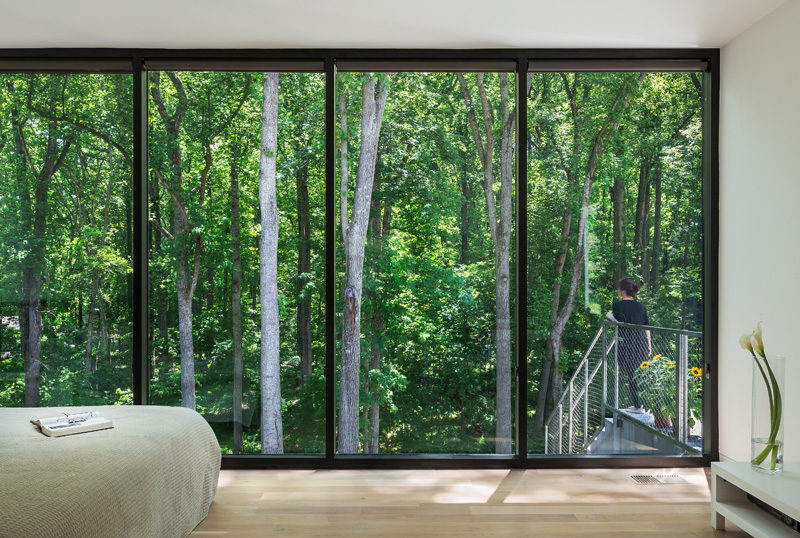 In this modern bedroom, floor-to-ceiling windows provide a view of the trees and allow plenty of natural light to fill the room.#Windows #Bedroom
