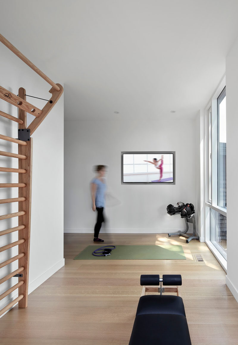 This modern house has an area that's dedicated to a small gym with space for a yoga mat to be positioned in front of a window. #HomeGym #Gym