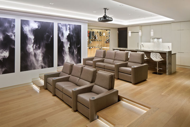 This basement is home to a theater room with tiered seating and a bar with built-in wine cellar.#HomeTheater #Basement