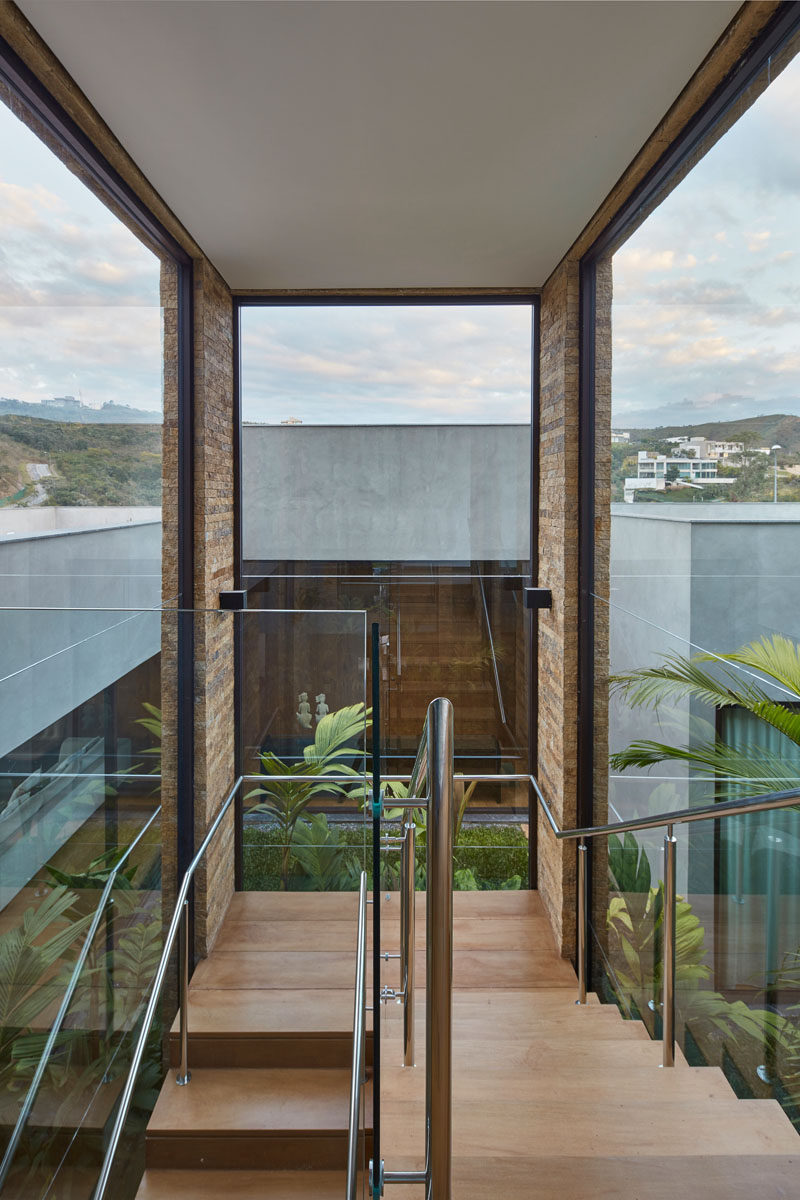 These wood stairs that lead to the second floor of this modern house are constructed over an internal garden, while large windows provide views of the surrounding landscape. #Stairs #Windows #ModernHouse