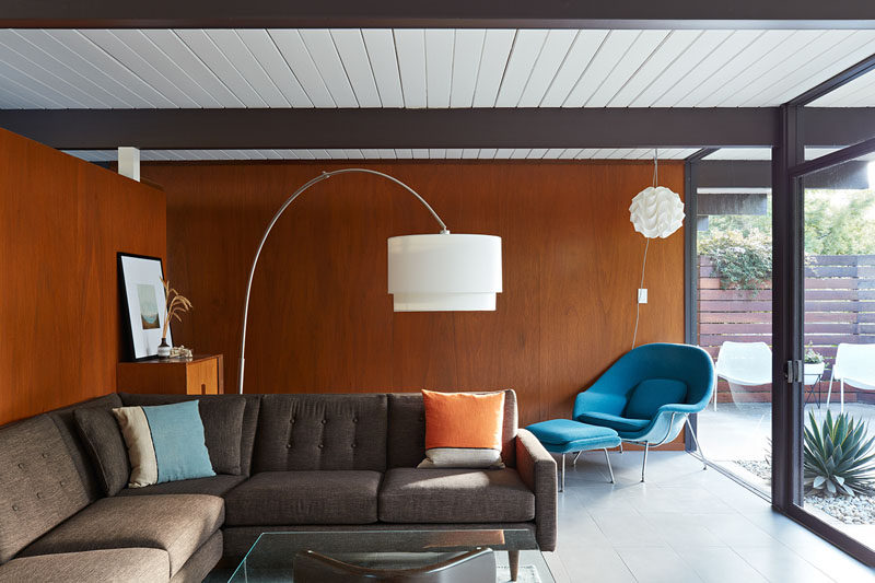 In this updated mid-century Eichler house, original paneling was re-stained to bring out the richness of the wood, like in the living room. #LivingRoom #WoodWalls