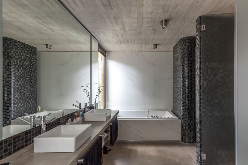 This modern bathroom has a bathtub that's positioned to look out of the window, while black and grey tiles add a darker element to the space. #ModernBathroom #Concrete