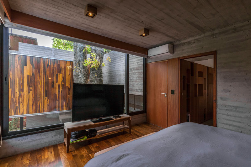In this modern bedroom, large windows allow the sunlight to brighten up the room and show off the established trees. #ModernBedroom #Windows