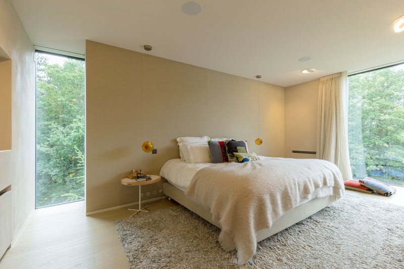 In this modern bedroom, a partial wall provides a place to anchor the bed in the room, while a large rug, light curtains and a big blanket create a cozy atmosphere. #Bedroom #InteriorDesign