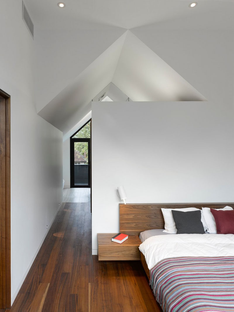In this modern bedroom, high white ceilings create a sense of openness, while wood floors and a wood bed frame add a sense of warmth to the room. #ModernBedroom #BedroomDesign