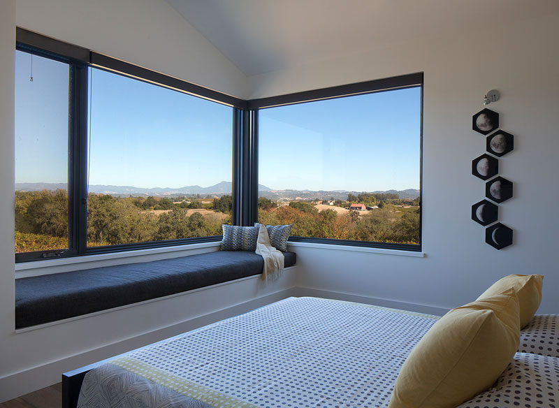 In this modern bedroom, a built-in window seat provides a place to take in the scenery from the windows. #WindowSeat #BedroomDesign #Windows