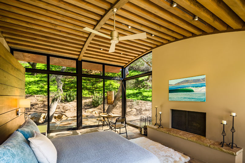 In this master suite, a curved ceiling makes the room feel large and bright, while a built-in fireplace with a Cherokee flagstone hearth, keeps the room feeling cozy on a cold night. #Bedroom #CurvedCeiling #Fireplace