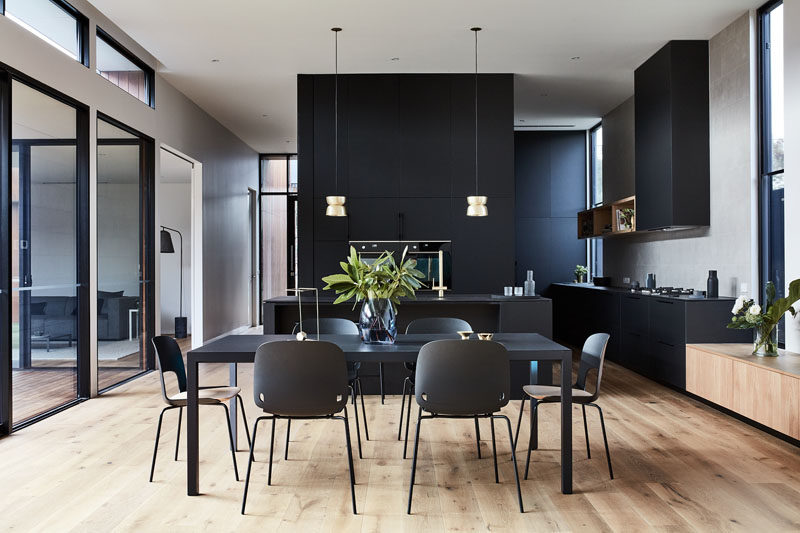 Matte black furniture in the dining room complements the matte black kitchen in this modern house. #MatteBlack #DiningRoom #Kitchen