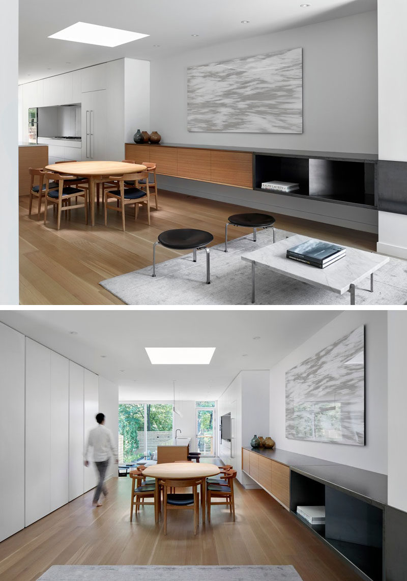 In this modern house, a built-in sideboard lines the wall, while white oak has been used for the wood flooring. A skylight that travels through all of the floors of the home, ends above the dining table,replacing the customary chandelier. #DiningRoom #Skylight #Sideboard