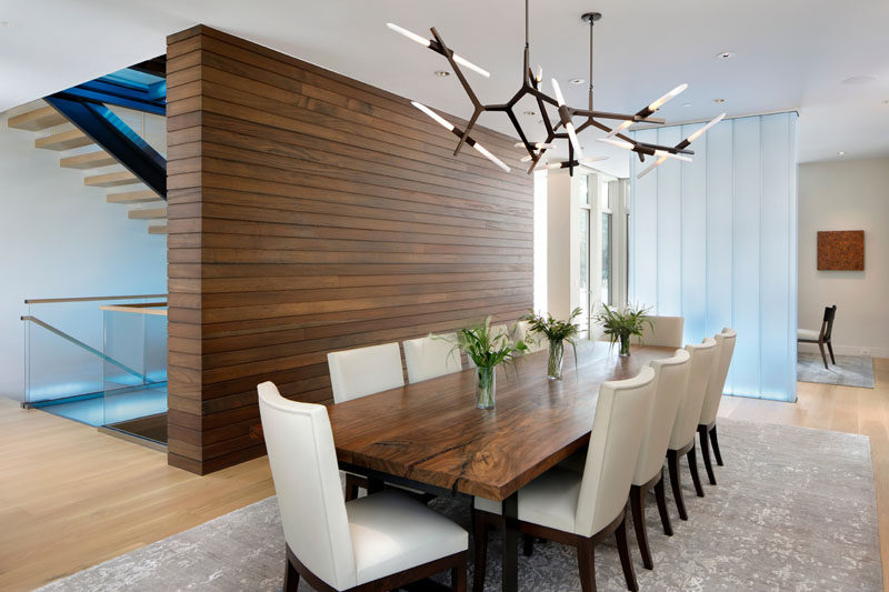 In this contemporary dining room sits beside a wood accent wall and a channel glass partition, while sculptural pendant lights add an artistic flair to the room. #DiningRoom #InteriorDesign