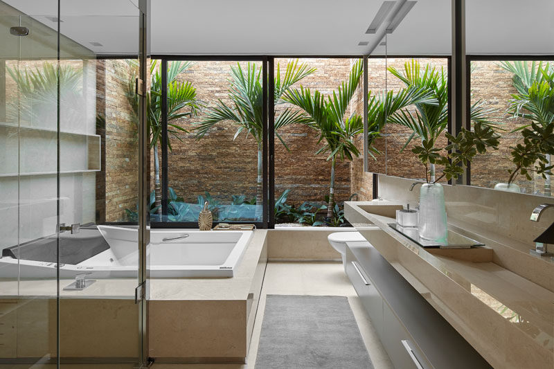 This modern bathroom has a private garden that helps to creates an almost tropical feeling. #ModernBathroom #Garden