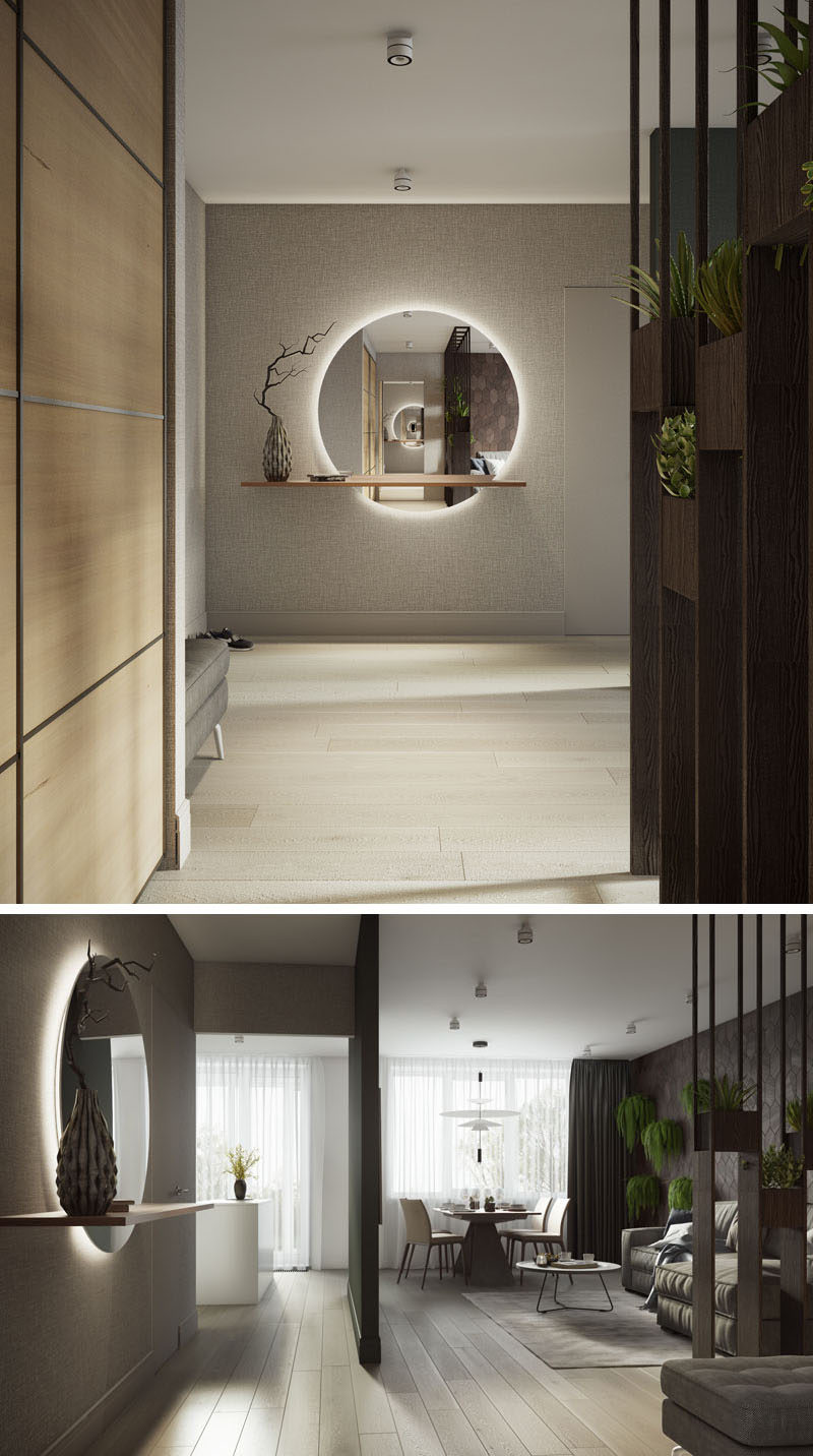 Upon entering this modern apartment, there's a large backlit mirror with a floating wood shelf.#ModernApartment #BacklitMirror