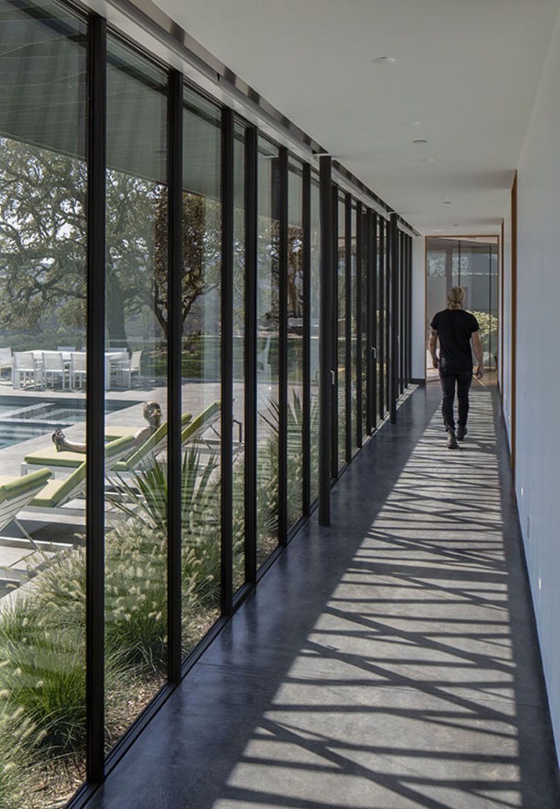 A long hallway with floor-to-ceiling windows connects the living areas of this modern house to the bedrooms. #ModernHallway #Windows