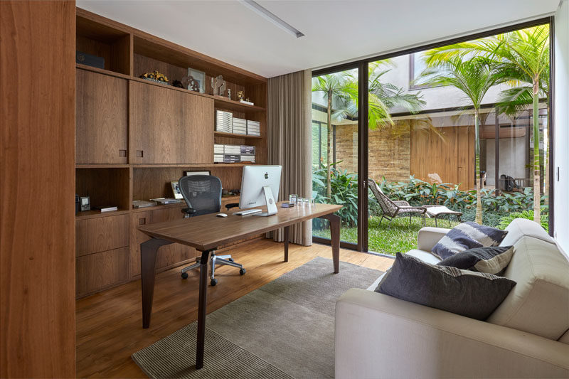 This modern home office with built-in wood shelving has access to an internal garden. #InternalGarden #HomeOffice #WoodShelving