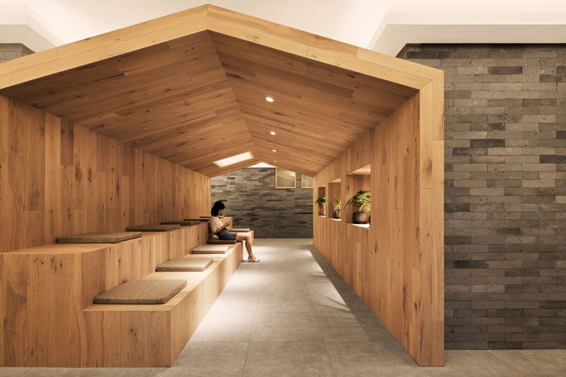 This modern hotel has a seating area housed in a 'little house' with long wood tiered seating and cushions. #ModernHotel #HotelDesign #Wood