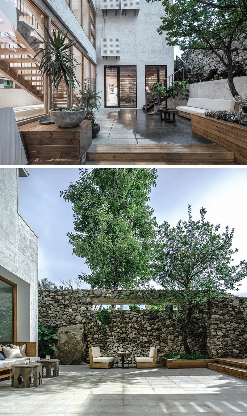 This modern hotel in China has outdoor spaces with wood planters, outdoor couches and a high stone wall. #OutdoorSpace #HotelDesign