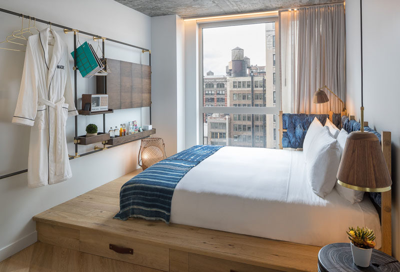 In this modern hotel rooms, the beds are raised up onto a wood platform, allowing for storage drawers to be tucked away underneath the bed. #ModernHotelRoom #PlatformBed #MADEHotel