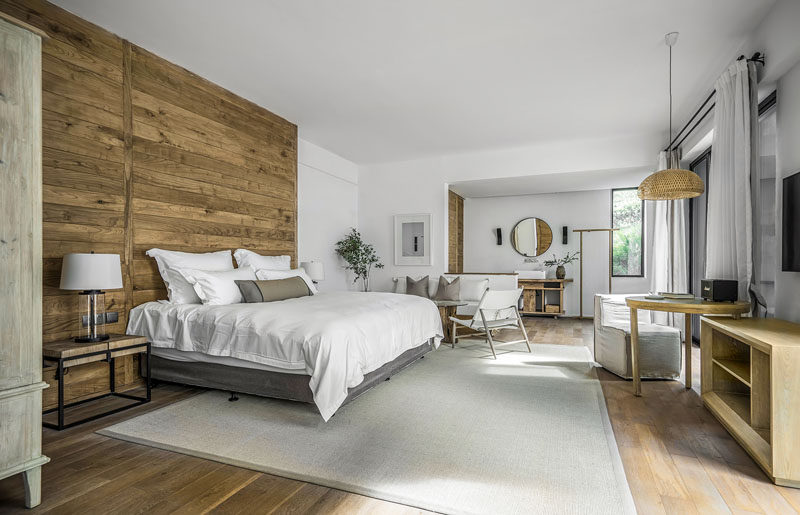 A wood accent wall gives this modern hotel room a unique look and provides the bed with a headboard. #ModernHotel #HotelRoom #WoodAccentWall