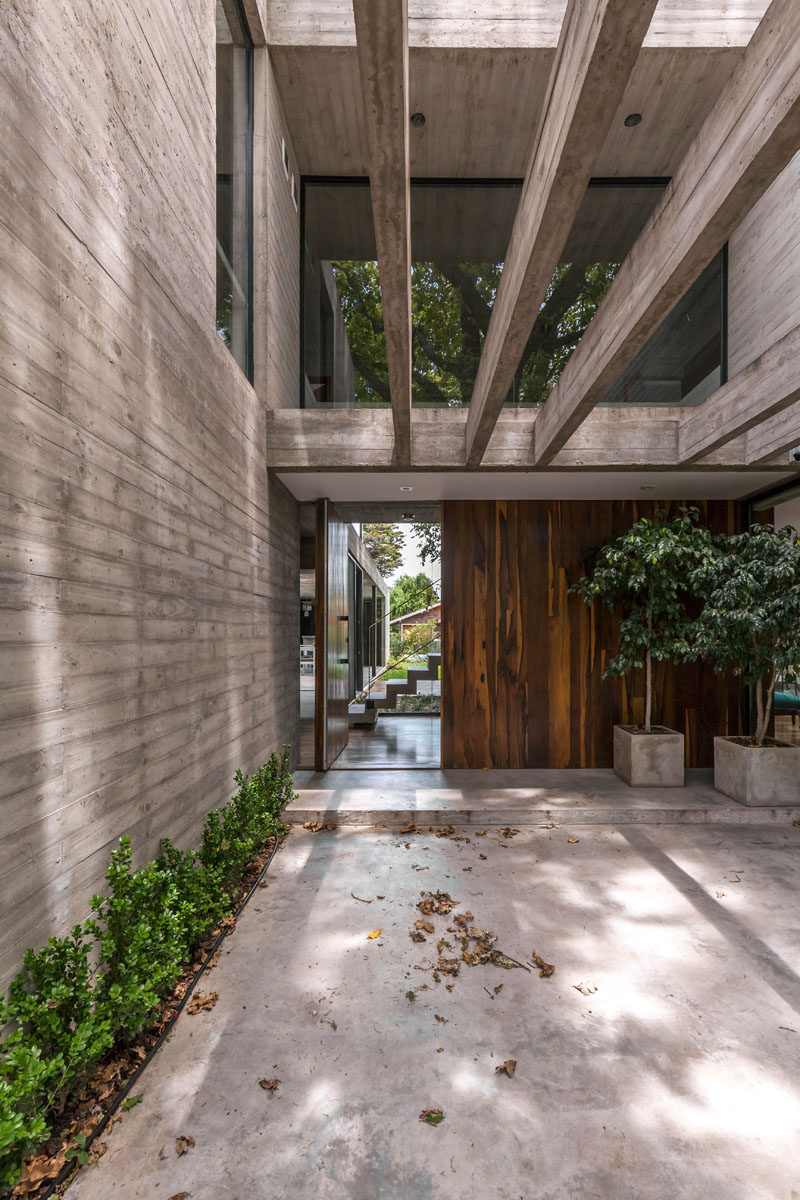 A large pivoting wood front door welcomes you to this modern house, and when open, it gives you a glimpse of the backyard.