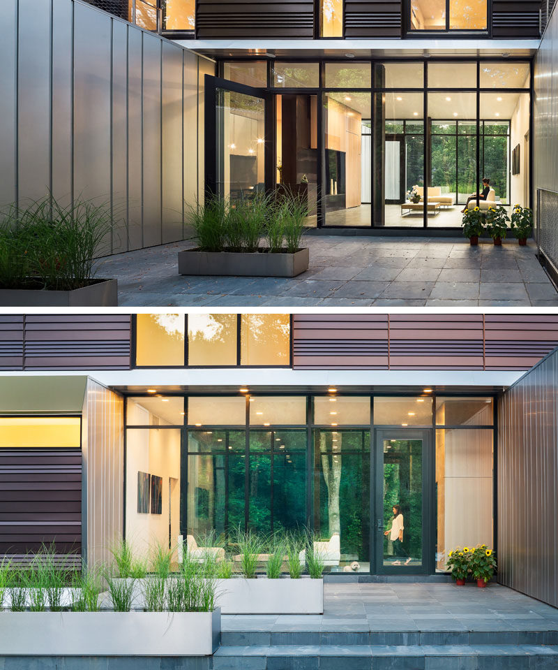 This modern house has a glass front door and matching windows are positioned between the various volumes of the house and welcomes you to a small sitting area. #FrontDoor #Windows